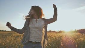 一个女孩从幸福跳在晚上太阳的日落 反对麦田背景  股票录像