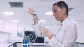 一个女性化验员转移一个蓝色液体样品到试管使用微球管,当坐在a时的一张桌上 股票视频