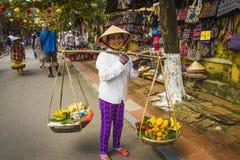 一个女性摊贩,卖果子在会安市` s古镇 库存照片