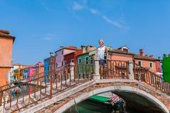 一个女性旅客在横跨一条运河的一座桥梁站立在Burano海岛上与许多五颜六色的房子的在背景中 免版税库存图片