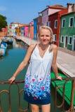 一个女性旅客在横跨一条运河的一座桥梁站立在Burano海岛上与许多五颜六色的房子的在背景中 库存照片