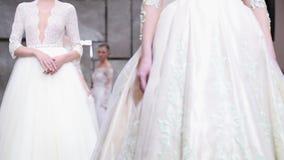 一个女性模型走美丽的时髦的白色婚礼礼服的跑道 股票录像