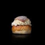 一个奶油色小圆面包,被生动描述反对黑背景 库存照片