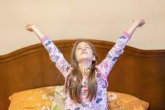一个好儿童女孩享受晴朗的早晨 早晨好在家 儿童女孩从睡眠醒 舒展在床上的女孩在 免版税库存图片