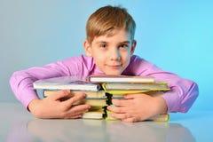 一个好奇少年拥抱书,当坐在书桌时 免版税库存图片