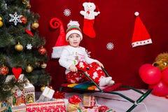 一个好男孩在圣诞树旁边坐 库存照片