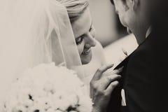 一个好妻子的光亮的微笑-新娘别针在未婚夫的一朵钮扣眼上插的花 库存照片