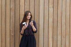 一个妇女读书正文消息的半身画象在她的手机的,当站立与时拿走咖啡户外, 库存照片