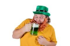 一个妖精帽子的一个微笑的愉快的肥胖人用在演播室的绿色啤酒 他庆祝圣帕特里克 免版税库存照片