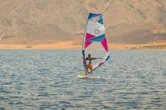 一个委员会的风帆冲浪者在风帆下在风平浪静移动在低速, 免版税库存图片