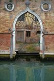一个威尼斯式大厦的古老哥特式入口与一点内部法院的由运河,威尼斯,意大利 免版税库存照片