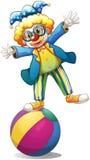 一个嬉戏的男性小丑在球顶部 免版税库存照片