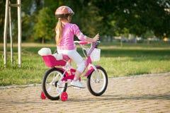 一个嬉戏的滑稽的女孩的画象一个桃红色安全帽的在她 库存照片