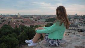 一个孤独的女孩坐观察平台的墙壁并且看  影视素材