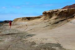 一个孤立徒步旅行者沿干旱的石化火山的在El Medano,特内里费岛的熔岩落寞风景走 库存照片