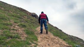 一个孤立旅客攀登山峰 图库摄影
