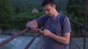 一个孤立游人在有一个手机的一座桥梁站立 影视素材