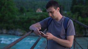 一个孤立游人在有一个手机的一座桥梁站立 股票视频