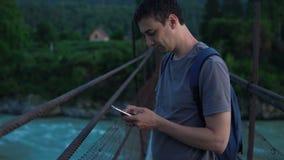 一个孤立游人在有一个手机的一座桥梁站立 股票录像