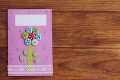 一个孩子做的贺卡为母亲节,父亲节,生日3月8日, 与一朵花的纸牌从木按钮 库存图片