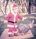 一个孩子在圣诞老人衣服推挤驯鹿玩偶,浓缩的unfriend 免版税库存图片