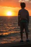 一个孩子的剪影在海前面的日落的 免版税库存照片