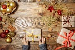 一个孩子的手特写镜头有礼物的 在木桌上的圣诞节装饰与拷贝空间 免版税库存照片