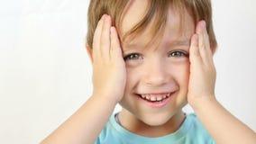 一个孩子的特写镜头有喜悦和微笑的看照相机,握他的在他的头后的手,包括他的耳朵 股票视频