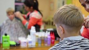 一个孩子的理发有剪刀的在理发店 股票视频