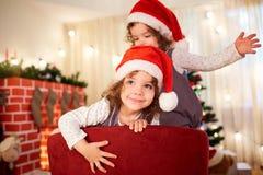 一个孩子的画象圣诞节的 圣诞老人帽子的a卷曲逗人喜爱的女孩 免版税库存照片