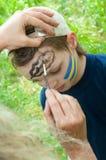 一个孩子的画象有他的被绘的面孔的 库存照片