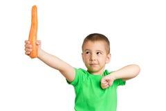 一个孩子的画象用一棵红萝卜在手上 库存图片