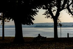一个安装的人在长凳和看湖的剪影在两棵树之间的 意大利,阿罗纳 图库摄影