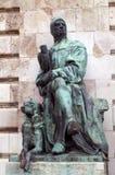 一个安装的人的雕象有一只猎鹰的在他的手和一条狗上在他的脚 图库摄影