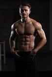 一个完全适合的肌肉年轻人的画象 库存照片