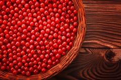 一个宏观轻的篮子用红浆果填装了 在黑暗的木背景的新鲜的雅致的无核小葡萄干 明亮的红色裂口无核小葡萄干 库存图片