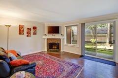 一个客厅的内部有壁炉和出口的对后院区域 免版税库存图片