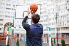一个室外体育场的一个蓝球运动员训练,投掷球入圆环,提起他的手 库存图片