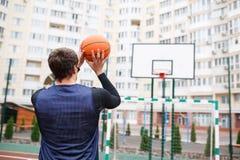 一个室外体育场的蓝球运动员训练与球 免版税库存照片