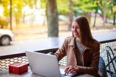 一个室外咖啡馆的一个女孩与膝上型计算机谈话通过录影电话 库存图片