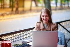一个室外咖啡馆的一个女孩与膝上型计算机谈话通过录影电话 免版税库存照片