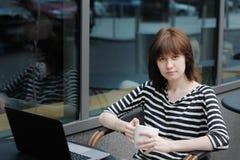 一个室外咖啡馆的女孩 免版税库存图片