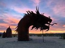 一个室外蛇雕塑的剪影在五颜六色的日出期间的 图库摄影