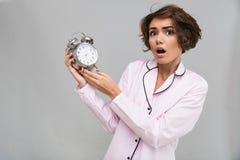 一个害怕的女孩的画象拿着闹钟的睡衣的 库存图片