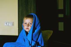 一个害怕的男孩在床上在晚上 儿童` s恐惧 免版税库存照片
