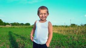 一个害羞的四岁的孩子的画象反对自然背景的,孩子调查照相机和微笑,然后看 股票录像