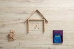 一个家庭的住宅房子在计算器和笔记本旁边 库存图片