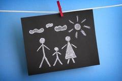 一个家庭的图画在黑纸的 免版税库存照片