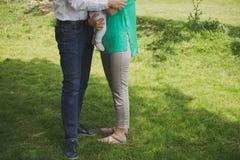 一个家庭的腿在草的与胳膊的婴孩 免版税库存照片