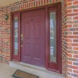一个家的方形的门面有一个红色大门的和反射性侧灯和窗口 库存图片